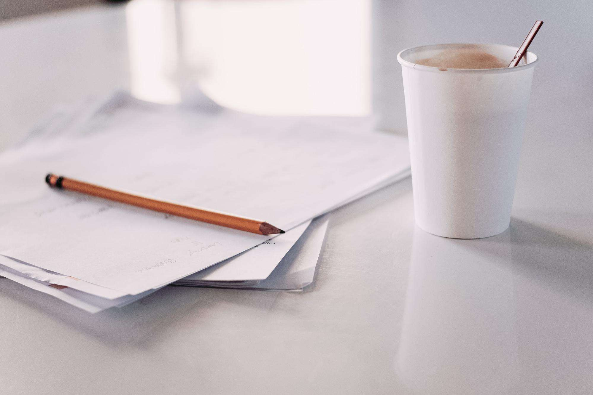 Papers on a desk with coffee